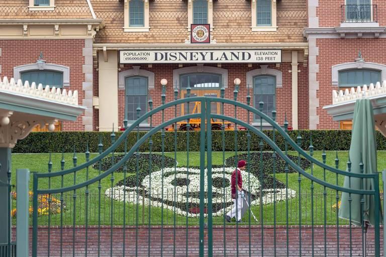 Portão fechado e atrás se vê gramado com formato do mickey