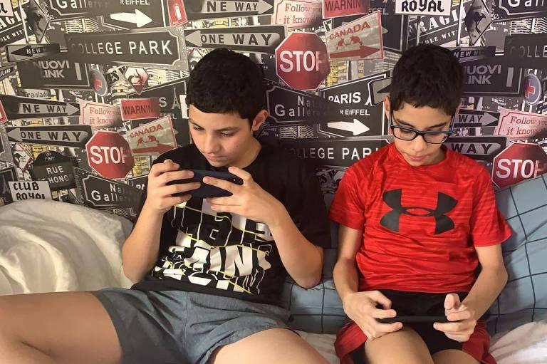 Gêmeos João Mauricio e Carlos Victor, 11 anos, usam o celular para estudar e se divertir durante a quarentena