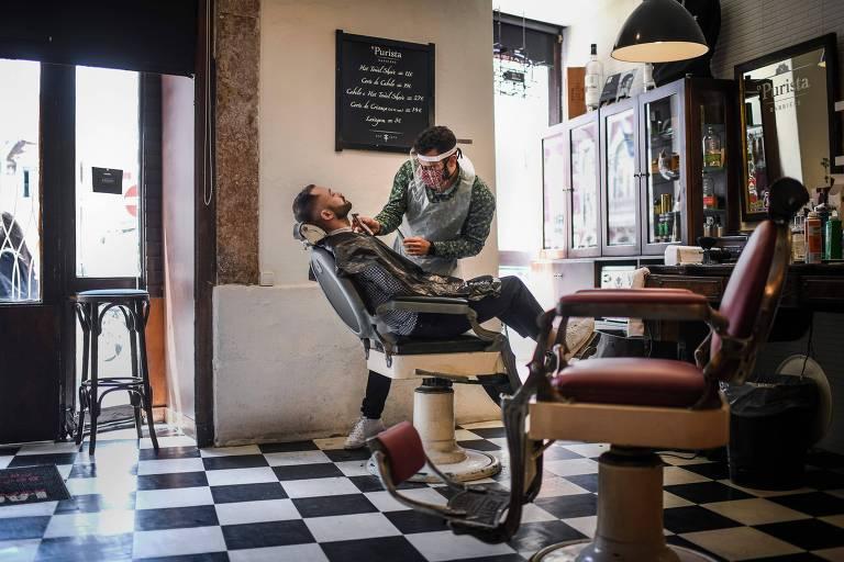 Barbeiro com máscara e proteção atende cliente em Lisboa