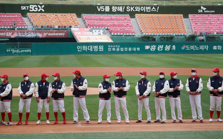 Com máscaras, jogadores de SK Wyverns e Hanwha Eagles participaram nesta terça-feira (5) do primeiro jogo da temporada regular de beisebol na Coreia do Sul. Esporte voltou ainda sem público no estádio, substituído por banners que simulam pessoas
