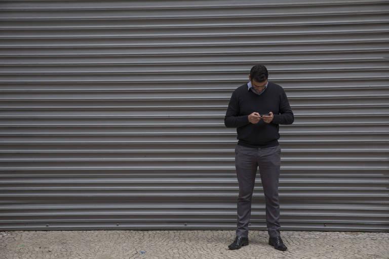 Homem usa celular no centro de São Paulo