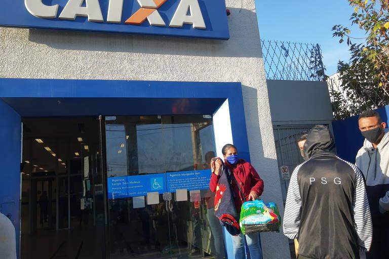 Pessoas usando máscara fazem fila na frente de uma agência da Caixa Econômica Federal para sacar o auxílio emergencial
