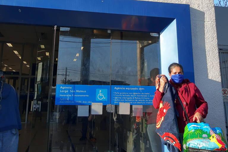 Mulher diante da porta de agência bancária em São Paulo