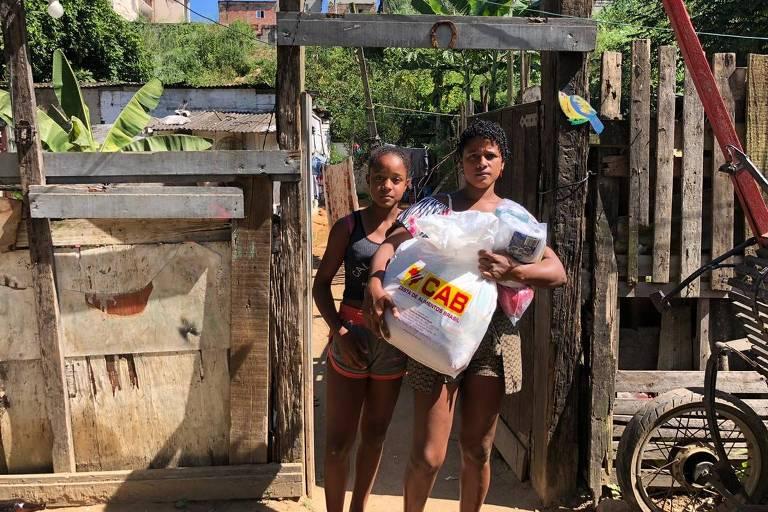 Duas mulheres na frente de uma casa de madeira segurando uma cesta básica