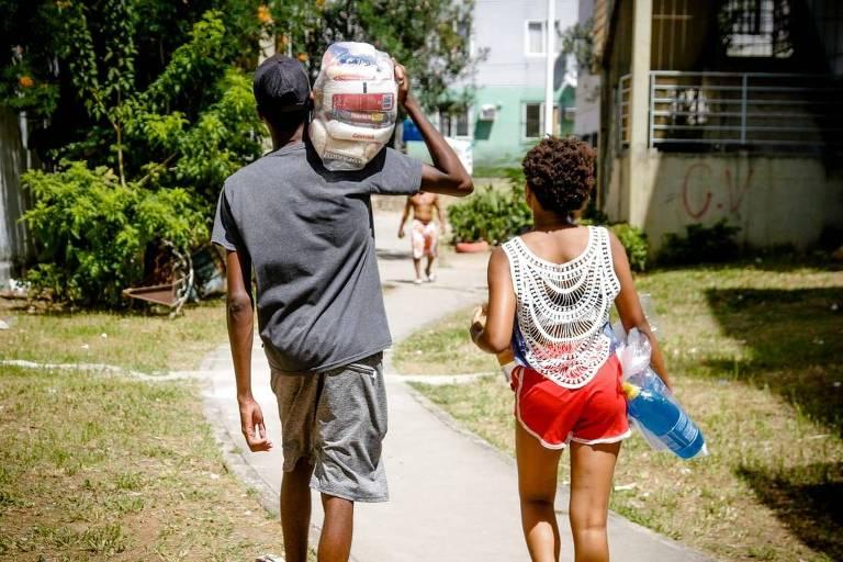 Um homem  e uma mulher caminham lado a lado, de costas, carregando uma cesta básica nos ombros
