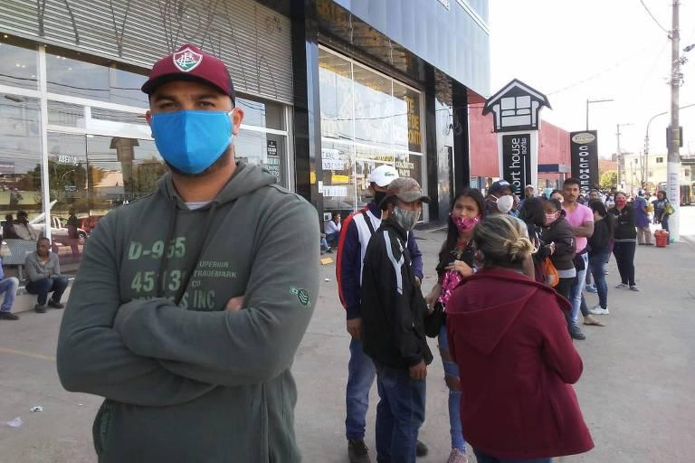 Homem de máscara em fila
