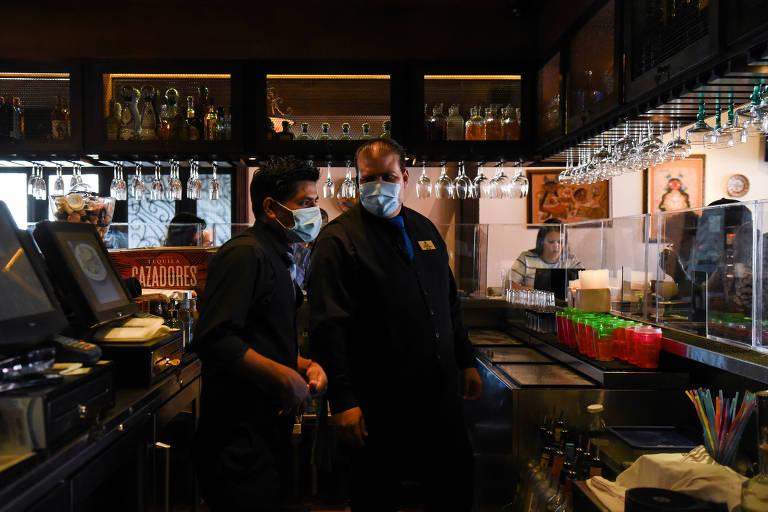 Bartenders de máscaras atendem clientes sentados atrás de divisória de vidro no restaurante Arnaldo Richard's Picos em Houston, no Texas