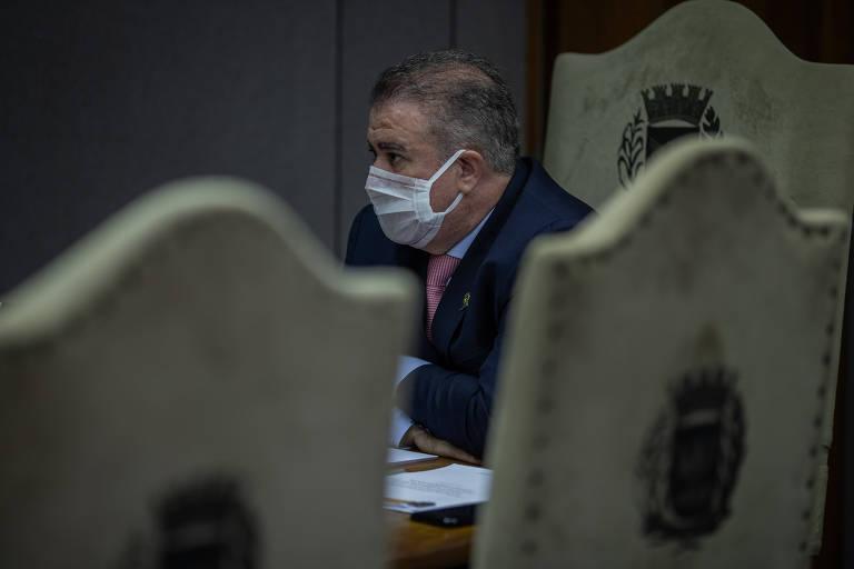 Jonas Donizette, em seu gabinete na prefeitura de Campinas; na foto, ele aparece, de terno e máscara cirúrgica, em meio a cadeiras vazias estampadas com um brasão