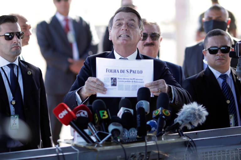 O presidente Jair Bolsonaro exibe reprodução da capa da edição desta terça (5) da Folha a jornalistas em frente ao Palácio da Alvorada