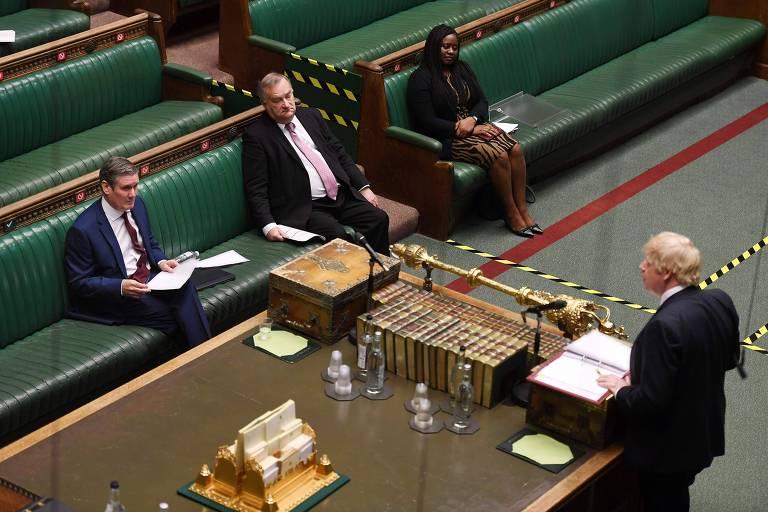 Em um Parlamento praticamente vazio devido às medidas de isolamento social, o premiê Boris Johnson (de costas) e o líder da oposição, Keir Starmer (sentado), debatem na sessão desta quarta (6)