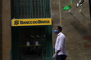 A man wearing a protective face mask and gloves walks in front of Banco do Brasil (Bank of Brazil) during the coronavirus disease (COVID-19) outbreak in Sao Paulo