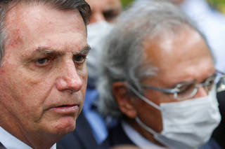 Brazil's President Jair Bolsonaro looks on next to Brazil's Economy Minister Paulo Guedes during a news conference after a meeting with President of Brazil's Supreme Federal Court Dias Toffoli, amid the coronavirus disease (COVID-19) outbreak in Brasilia