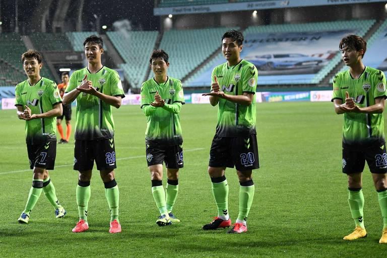 Dong-gook Lee (2º à direita), do Jeonbuk Hyundai Motors, comemora com companheiros após marcar o gol que deu a vitória ao seu time na abertura do campeonato