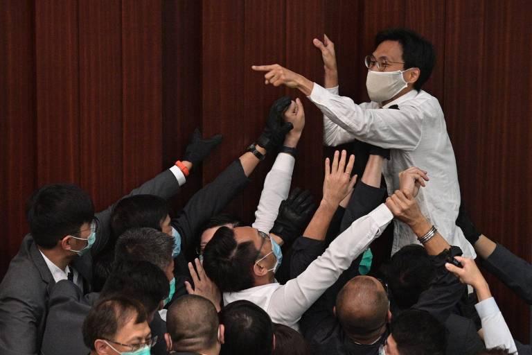 Eddie Chu Hoi-dick, parlamentar pró-democracia, tenta passar por cima de adversários para alcançar a cadeira da presidência