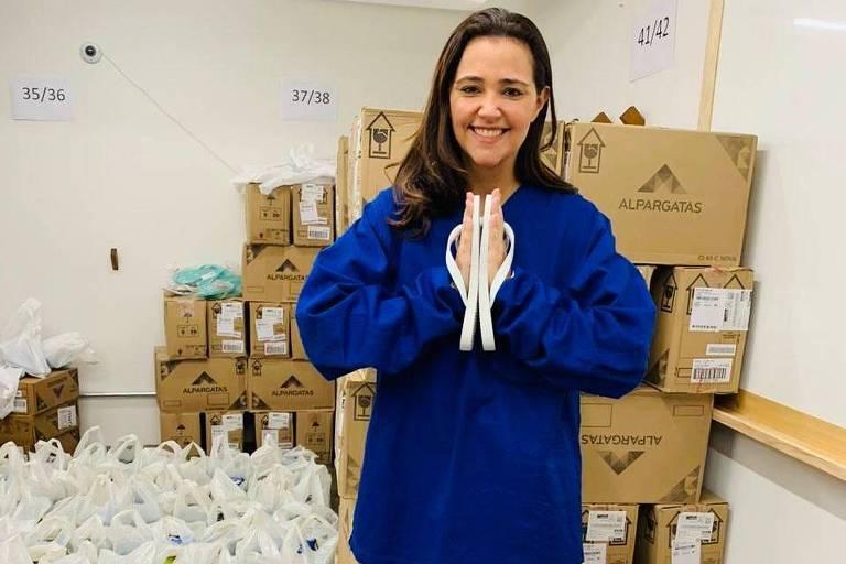 Médica em meio a sacolas de doações com um par de havaianas as mãos, que estão juntas na frente do peito, em sinal de agradecimento