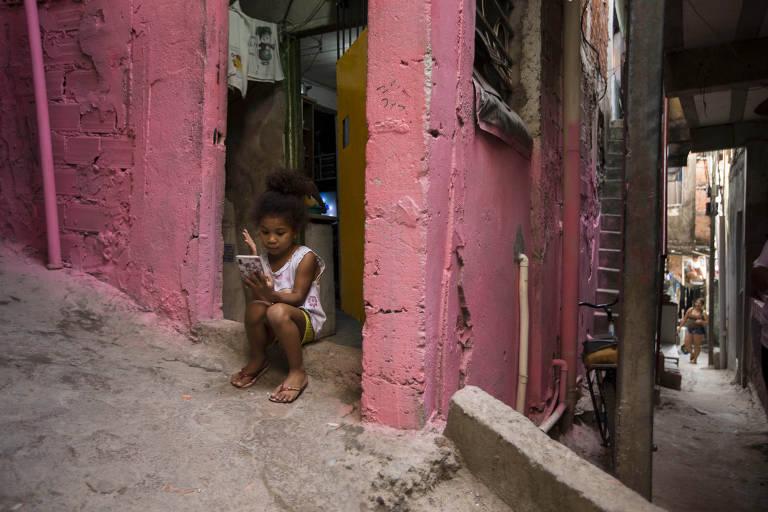 Menina usa celular na porta de casa