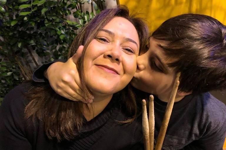 Filho beija a bochecha da mãe enquanto ela sorri para foto