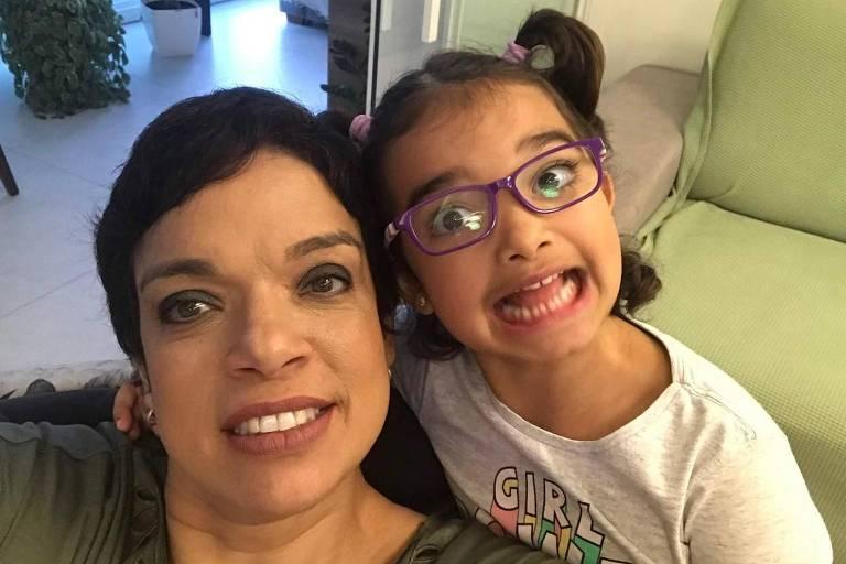 Criança de óculos e maria chiquinha sorri para a câmera ao lada da mãe, que tem cabelos curtos e também está sorrindo
