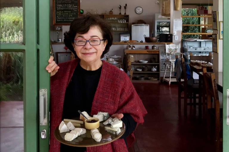 Heloisa encostada na porta de um restaurante com uma tábua com queijos na mão
