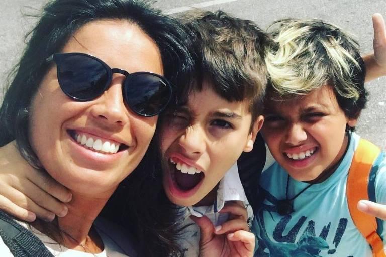 Os dois filhos estão abraçados com a mãe, que tira uma selfie com eles e sorri