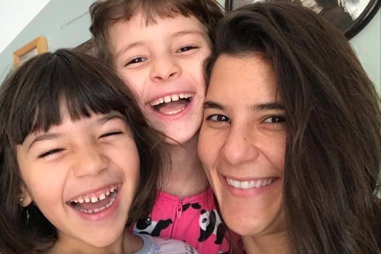 Mãe de cabelos lisos compridos sorri para foto ao lado das duas filhas pequenas