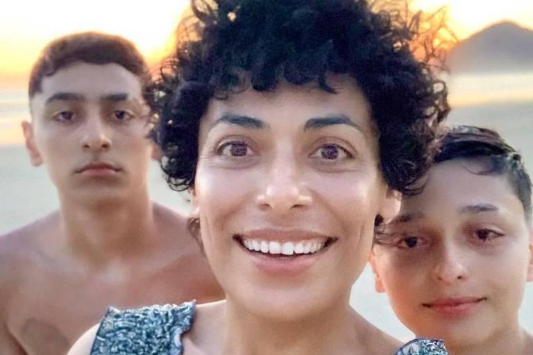 Mãe e dois filhos sorrindo em um fim de tarde na praia