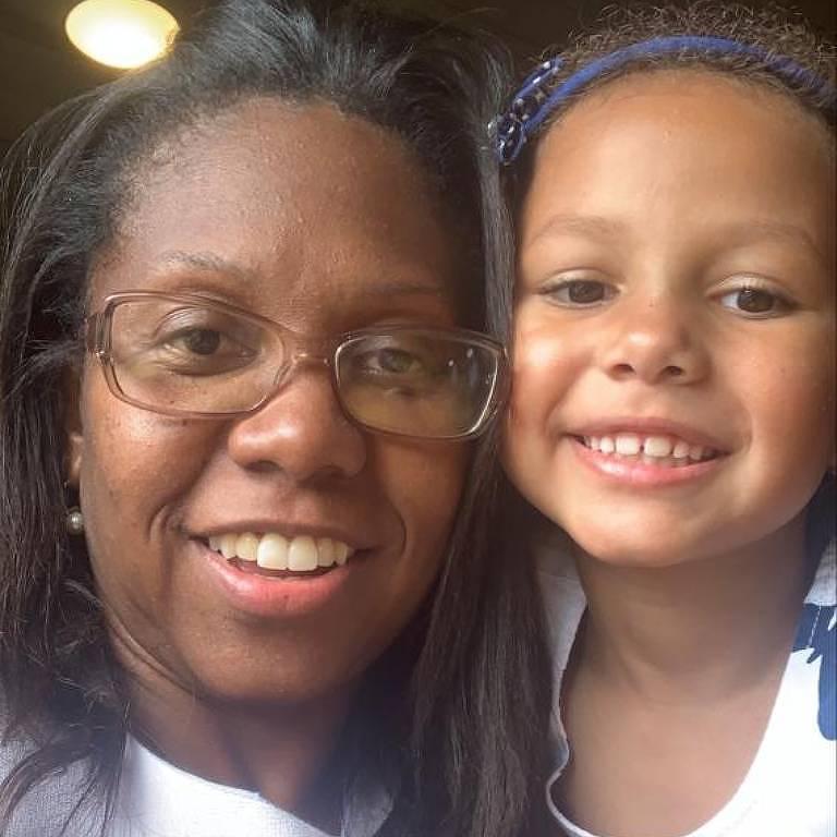 Mãe e filha, vestidas de branco, sorriem para foto