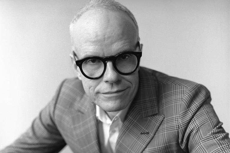 Homem de terno e óculos de armação preta em retrato preto e branco