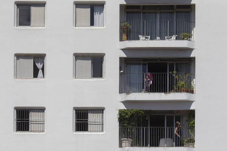 Criança toma sol em varanda de prédio em São Paulo