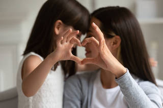 Mothers and daughters fingers showing heart symbol of love