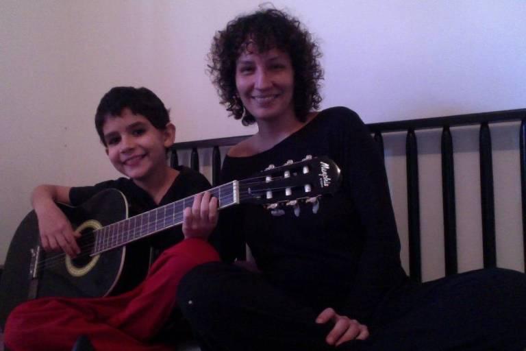 Menino segura violão ao lado da mãe