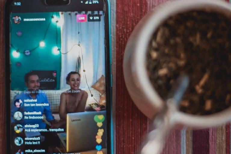 Casal argentino em celular, enquanto ministros de igreja evangélica virtualmente os casam