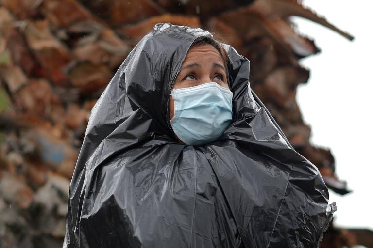 Juana Gomez, 50, espera na chuva enrolada em saco plástico preto