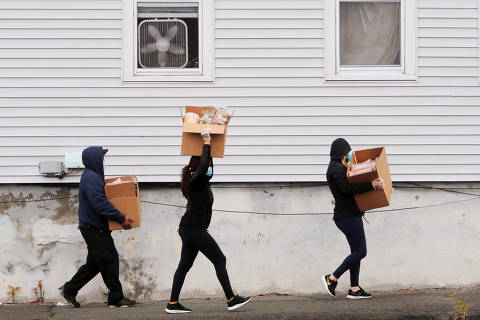 Residents carry boxes of free groceries distributed at a pop-up food pantry by the 101st Engineer Battalion of the Massachusetts Army National Guard amid the coronavirus disease (COVID-19) outbreak in Chelsea, Massachusetts, U.S., April 24, 2020.   REUTERS/Brian Snyder     TPX IMAGES OF THE DAY ORG XMIT: PPP-BKS20
