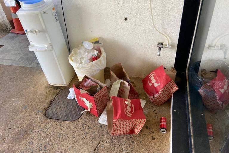 Ao lado de um bebedouro, há sacos do ifood jogados pelo chão, perto de uma lixeira