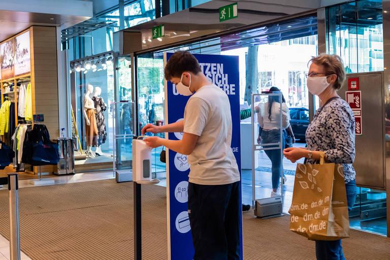 Ao entrar em loja, clientes higienizam as mãos em Berlim neste domingo