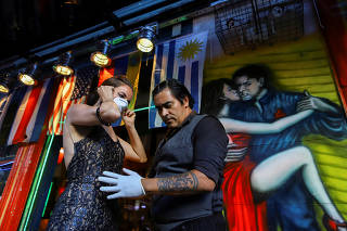 Makrina Anastasiadou puts on a face mask before dancing with her tango partner