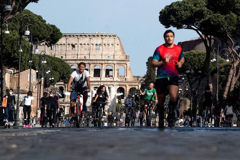 Moradores de Roma correm em rua da região central da cidade neste domingo (10)