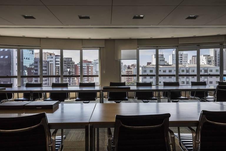 Escritório com mesas coladas e cadeiras vazias, com janelas grandes com vista para prédios