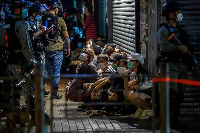 Manifestantes sentados no chão cercados por policiais