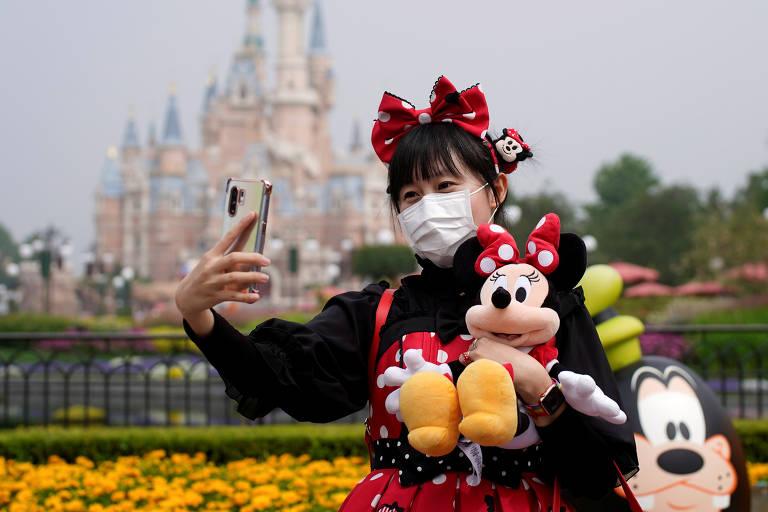 Mulher com máscara e tiara da Minnie segura bicho de pelúcia e posa para selfie com castelo de princesa ao fundo