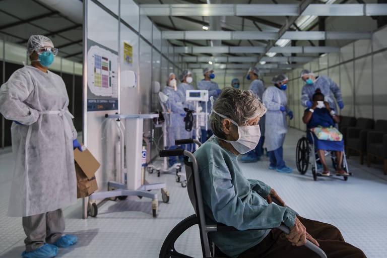 Mulher octagenária de máscara cirúrgica em cadeira de rodas é vista de perfil, com corredor hospitalar em perspectiva