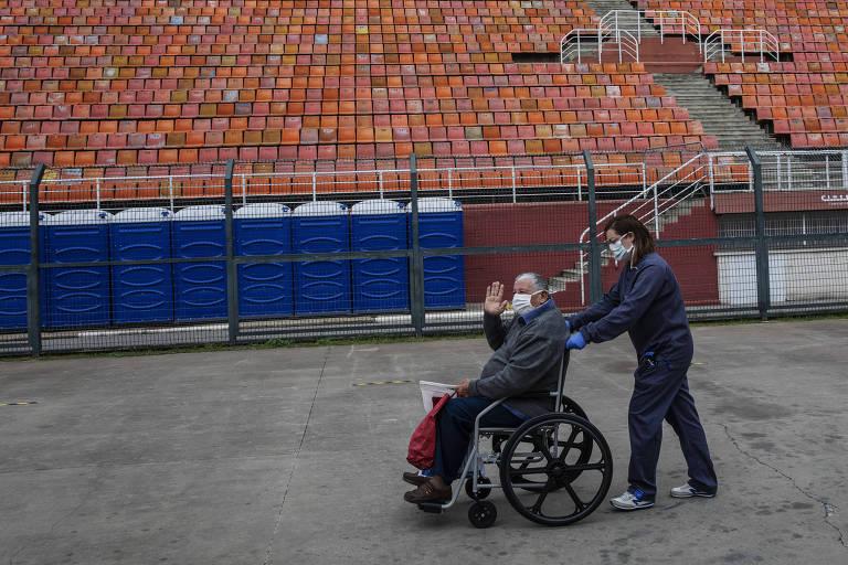 Homem idoso em cadeira de rodas, empurrado por mulher, ambos de máscaras, acena ao passar diante de arquibancada
