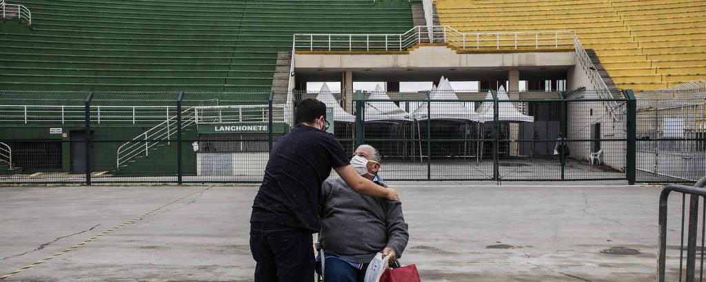 Homem idoso em cadeira de rodas abraça homem de meia idade, de costas, diante de arquibancadas verdes e amarelas
