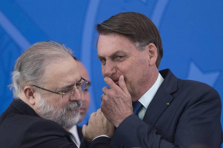 Bolsonaro cochicha algo para Augusto Aras durante evento no Palácio do Planalto, em abril passado