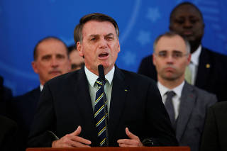 Brazil's President Jair Bolsonaro reacts while addressing the media during a news conference at the Planalto Palace in Brasilia