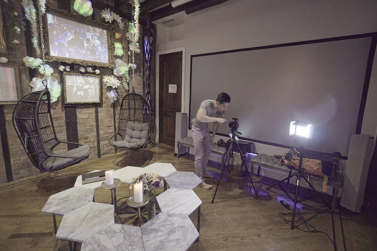 """O ator Kenneth Play prepara sua casa para filmas cena de filme """"Sex and Love in the Time of Quarantine""""; no filme, ele, que está sozinho no isolamento, se vale da masturbação; na foto, vemos o ator ajustando uma câmera numa sala com cadeiras de balanço penduradas no teto e uma mesa feita de peças hexagonais"""