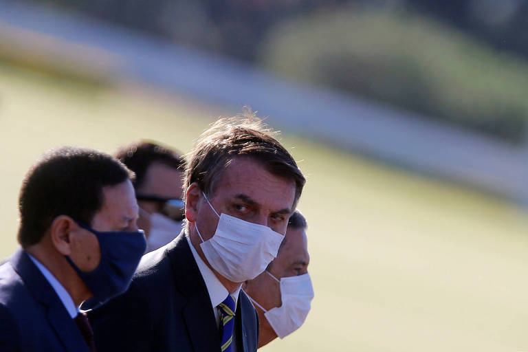 Bolsonaro caminha com ministros em direção à cerimônia de hasteamento da bandeira por vítimas do coronavírus