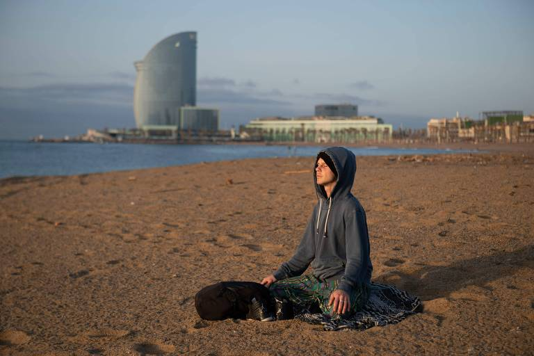 Homem medita enquanto pratica ioga na praia de Barceloneta