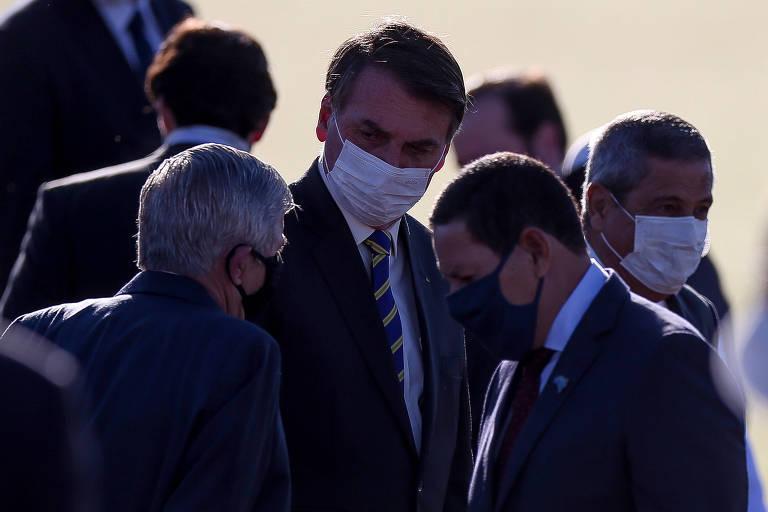 O vice-presidente Mourão (à dir.), com o presidente Bolsonaro e o ministro do Gabinete de Segurança Institucional, Augusto Heleno, durante hasteamento da bandeira no Palácio da Alvorada nesta terça (12)